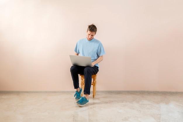 Un jeune homme travaillant à la maison avec un ordinateur portable, un mode de vie indépendant en ligne assis près du mur isolé