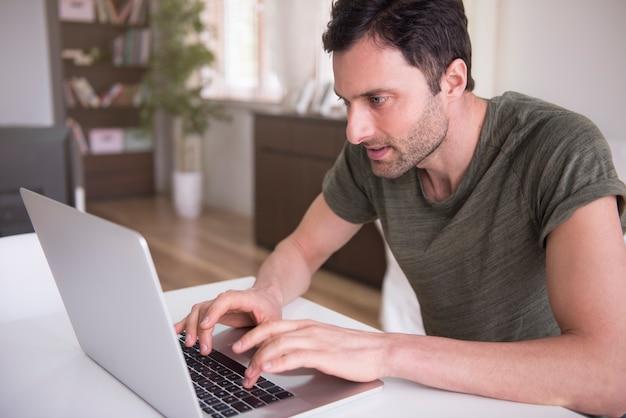 Jeune homme travaillant à la maison avec son ordinateur portable