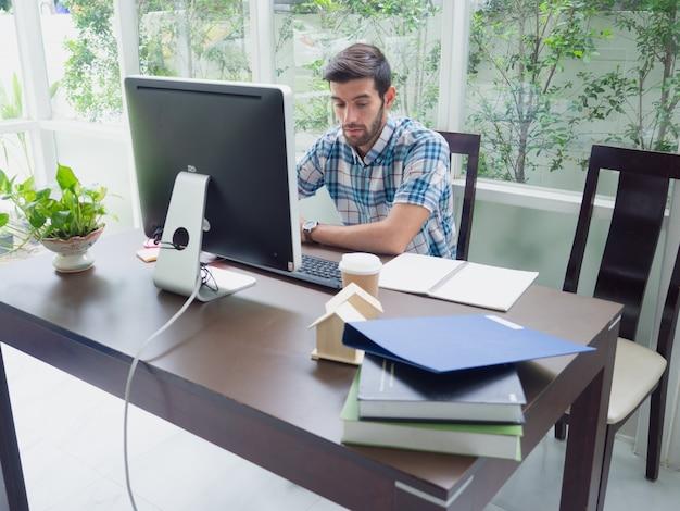 Jeune homme travaillant à la maison