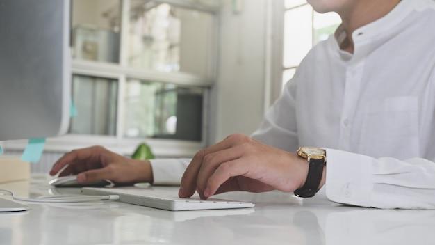 Jeune homme travaillant sur ordinateur à domicile, homme d'affaires utilisant un ordinateur à la maison, travail à domicile, étude en ligne.