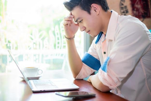 Jeune homme travaillant avec un ordinateur portable au café