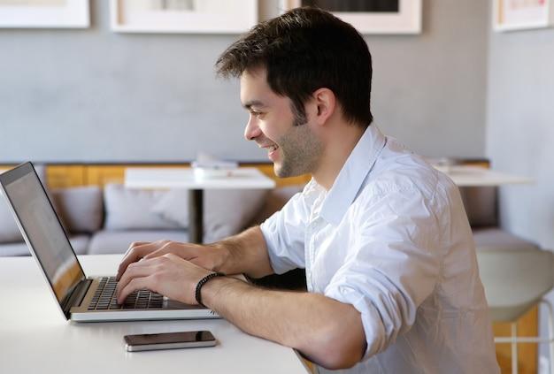 Jeune homme travaillant sur un ordinateur portable à l'intérieur