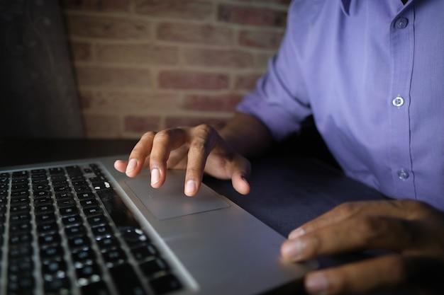 Jeune homme travaillant sur un ordinateur portable volant des données personnelles
