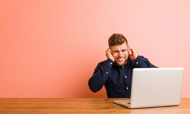 Jeune homme travaillant avec son ordinateur portable couvrant les oreilles avec ses mains.