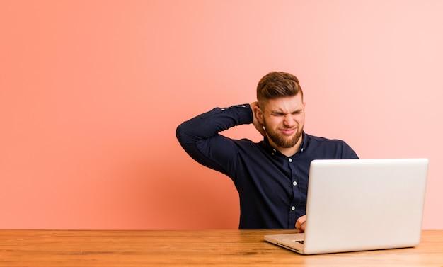 Jeune homme travaillant avec son ordinateur portable souffrant de douleurs au cou en raison de son mode de vie sédentaire.