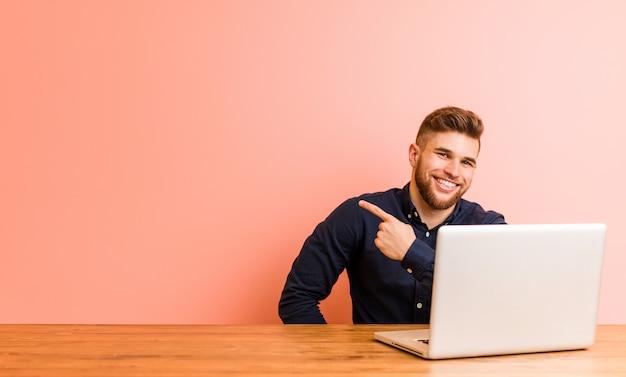 Jeune homme travaillant avec son ordinateur portable en souriant et en pointant de côté, montrant quelque chose dans un espace vide.