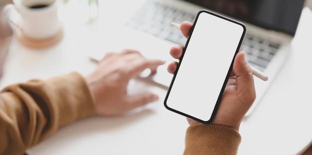 Jeune homme travaillant sur son projet en tapant sur un ordinateur portable et tenant un smartphone