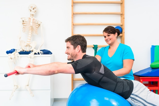 Jeune homme travaillant en thérapie physique sur ballon suisse avec bâton de gymnastique
