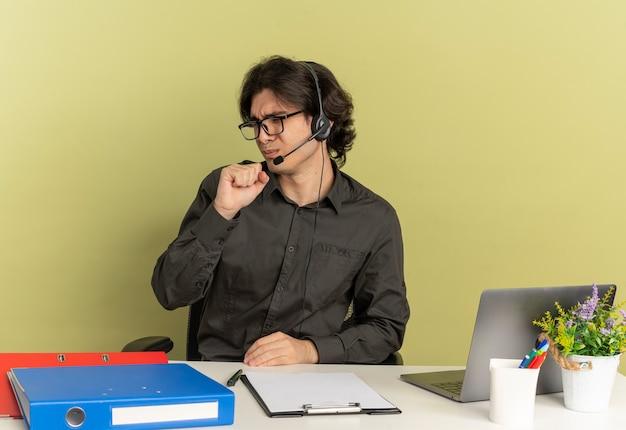 Jeune homme de travailleur de bureau agacé sur les écouteurs dans des lunettes optiques est assis au bureau avec des outils de bureau à l'aide d'un ordinateur portable tient le poing à la bouche isolé sur fond vert avec espace de copie