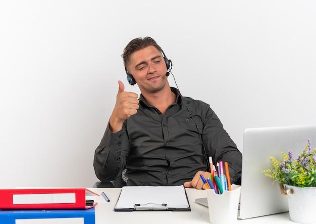 Jeune homme de travailleur de bureau blonde confiante sur les écouteurs est assis au bureau avec des outils de bureau regardant ordinateur portable thumbs up