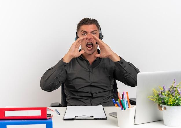 Jeune homme travailleur de bureau blonde furieuse sur les écouteurs est assis au bureau avec des outils de bureau à l'aide d'un ordinateur portable crie tenant la main à la bouche isolé sur fond blanc avec espace copie