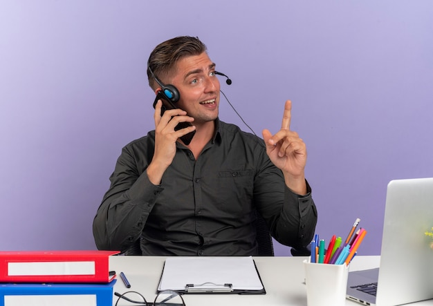 Jeune homme de travailleur de bureau blonde surpris sur les écouteurs est assis au bureau avec des outils de bureau à l'aide d'un ordinateur portable parle sur téléphone pointant vers le haut isolé sur fond violet avec copie espace