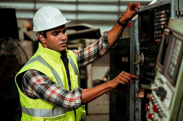 Jeune homme travailleur industriel travaillant avec une machine en métal en usine avec de nombreux équipements