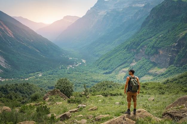 Jeune homme trekking au sommet d'une montagne verte pendant le coucher du soleil