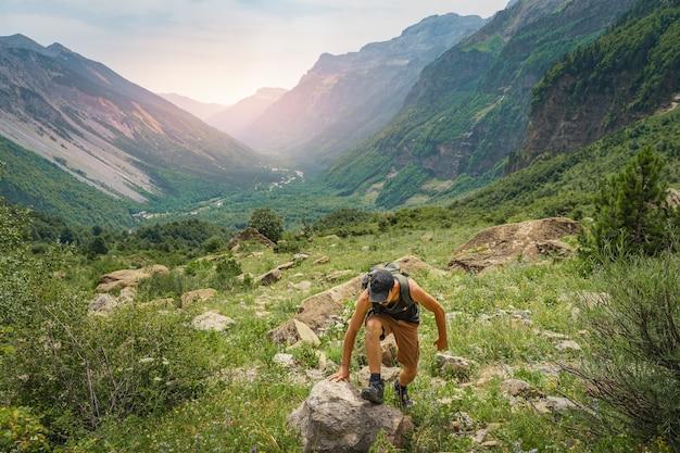 Jeune homme trekking au sommet d'une montagne verte