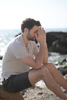 Jeune homme triste déprimé s'asseyant sur une plage de mer, paumes sur le visage