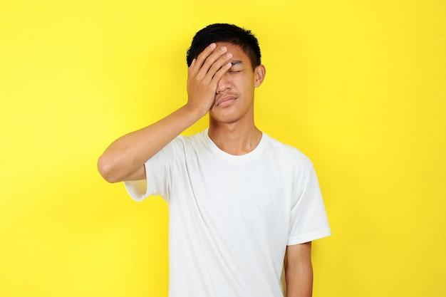 Jeune homme triste fermer l'un de ses yeux avec sa main, isolé sur fond jaune