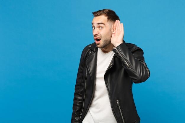 Un jeune homme triste, frustré et inquiet, mal rasé, en t-shirt blanc à veste noire, essaie de vous entendre isolé sur un portrait en studio de fond de mur bleu. concept de mode de vie des émotions sincères des gens. maquette de l'espace de copie.