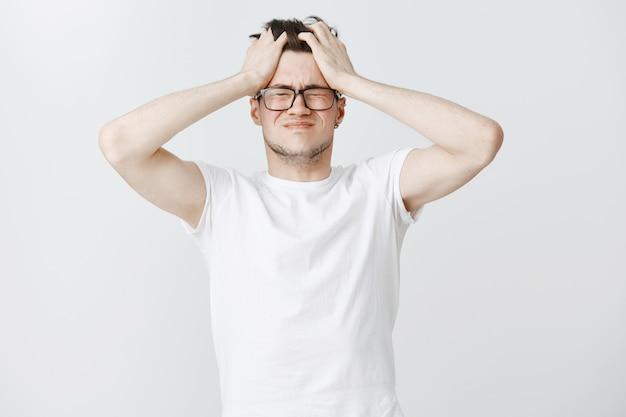 Un jeune homme troublé et épuisé saisit la tête et ferme les yeux après avoir trop réfléchi