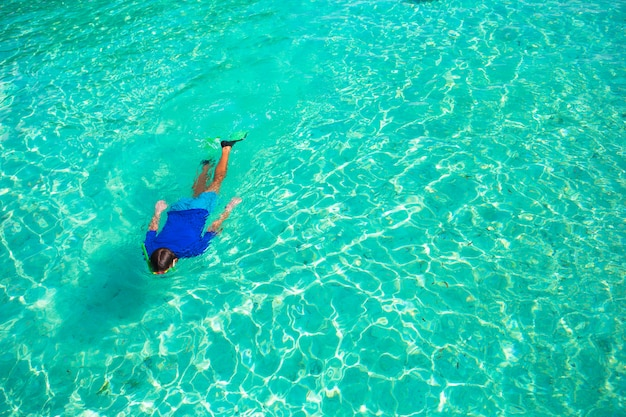 Jeune homme avec tuba dans les eaux turquoises claires