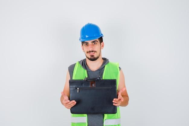 Jeune homme en uniforme de construction tenant une boîte à outils de construction avec les deux mains et ayant l'air heureux
