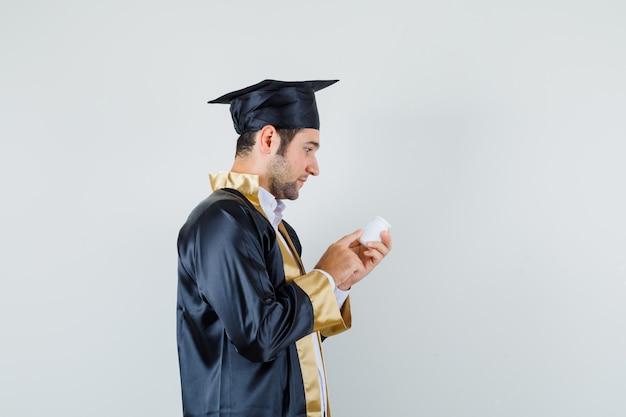 Jeune homme en uniforme de diplômé lisant des informations sur une bouteille de pilules et à la recherche de curiosité.