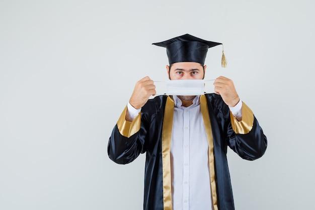 Jeune homme en uniforme de diplômé portant un masque médical et regardant prudemment, vue de face.