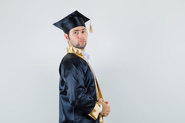 Jeune homme en uniforme diplômé tenant sa robe et à la confiance.