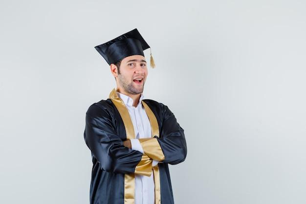 Jeune homme en uniforme d'études supérieures debout avec les bras croisés et à la fierté, vue de face.