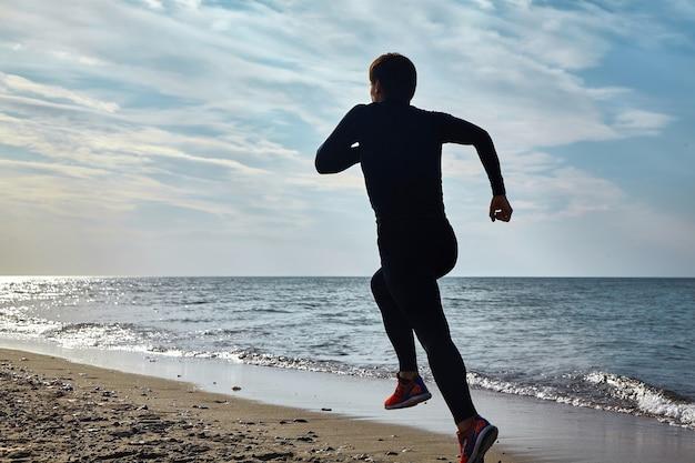 Un jeune homme en uniforme de sport longe le bord de mer. exercices d'aérobie pour la santé cardiaque