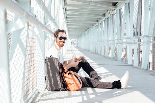 Jeune homme urbain parlant au téléphone intelligent voyageant à l'intérieur de l'aéroport. casual jeune homme d'affaires portant une veste de costume. beau modèle masculin. jeune homme avec téléphone portable à l'aéroport en attendant