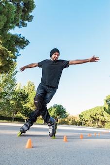 Jeune homme urbain sur patins à roulettes sur la route à l'heure d'été. concept de rouleau