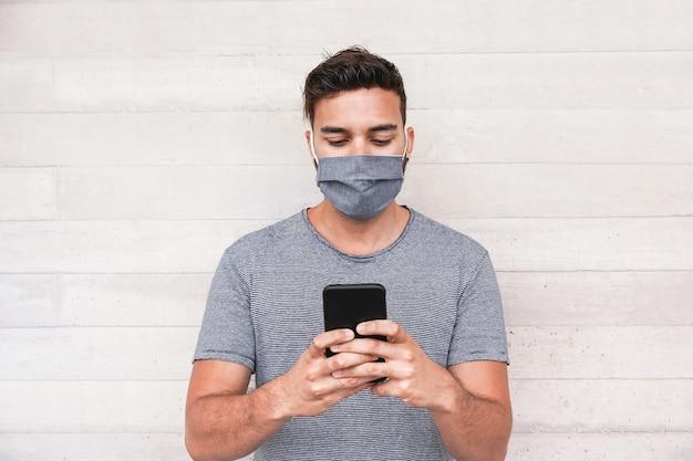 Jeune homme utilisant une application de téléphone mobile tout en portant un masque protecteur pendant l'épidémie de coronavirus - un gars du millénaire wathing vidéos sur smartphone - covid 19 concept de mode de vie et de technologie