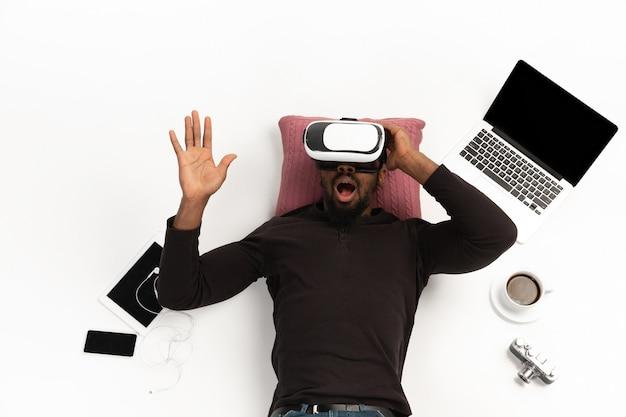Jeune homme utilisant un casque vr entouré de gadgets isolés