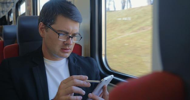 Jeune homme utilisant une cellule pour naviguer en ligne dans le train