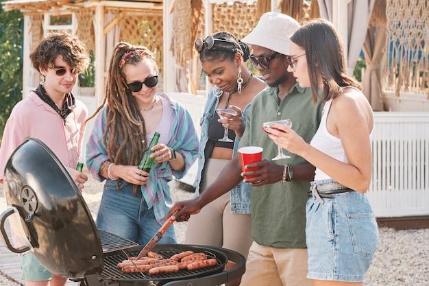 Jeune homme utilisant un couteau intelligent pour piquer des hot-dogs grillés et vérifier s'ils sont prêts à manger