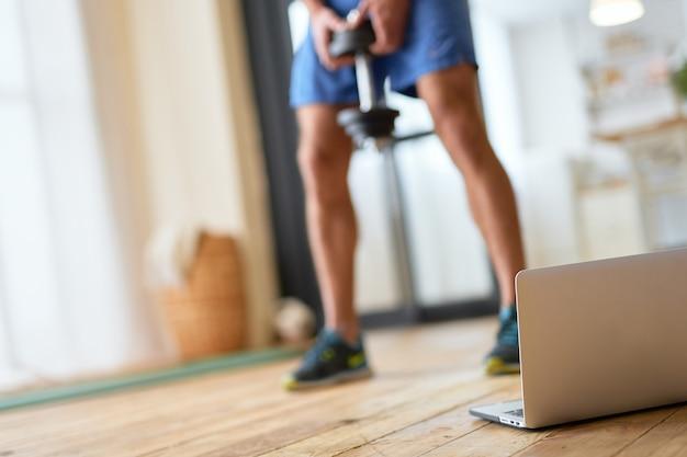 Jeune homme utilisant un ordinateur portable moderne pendant l'entraînement à domicile