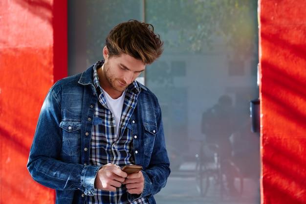 Jeune homme utilisant un smartphone en plein air