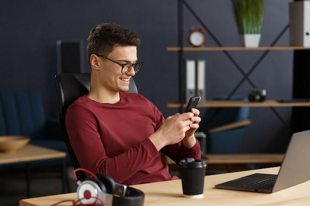 Jeune homme utilisant un smartphone et souriant. heureux homme d'affaires utilisant des applications de téléphonie mobile, sms, navigation sur internet, regardant un smartphone. concept de jeunes travaillant avec des appareils mobiles.