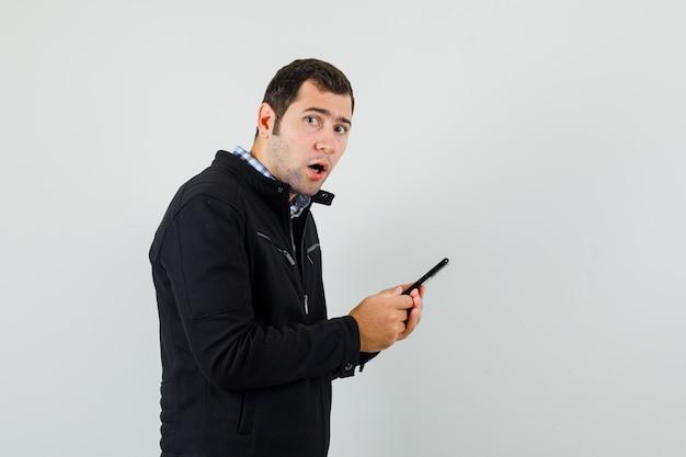 Jeune homme utilisant un téléphone portable en chemise, veste et à la recherche de surprise. .