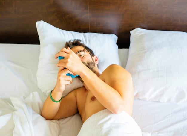 Jeune homme utilisant un téléphone portable dans le lit