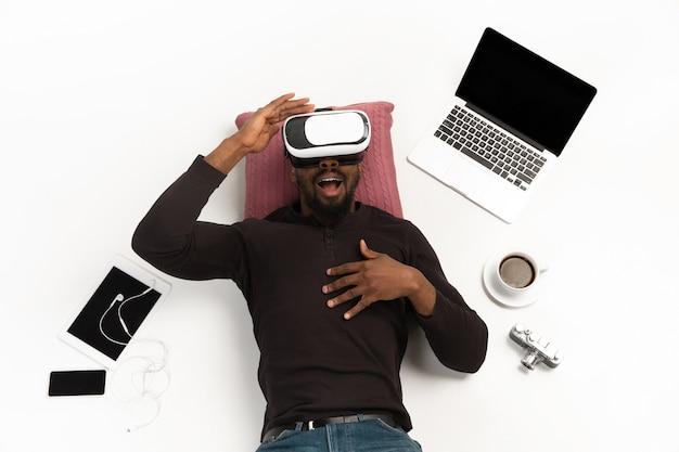 Jeune homme utilisant vrheadset entouré de gadgets