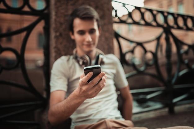 Jeune homme, utilisation, téléphone portable, dehors