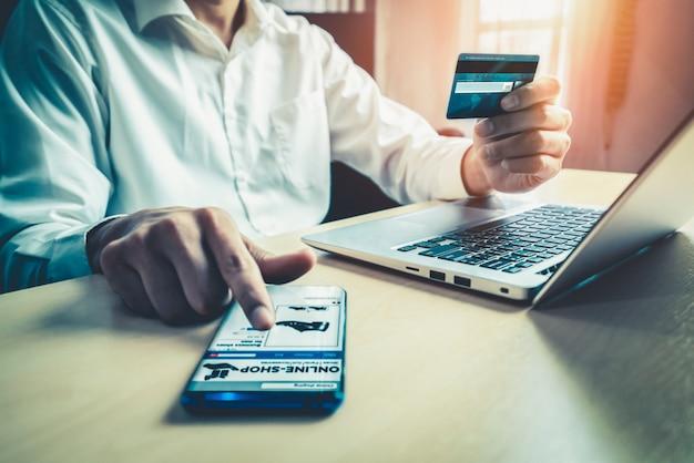 Jeune homme utilise une carte de crédit pour les achats en ligne