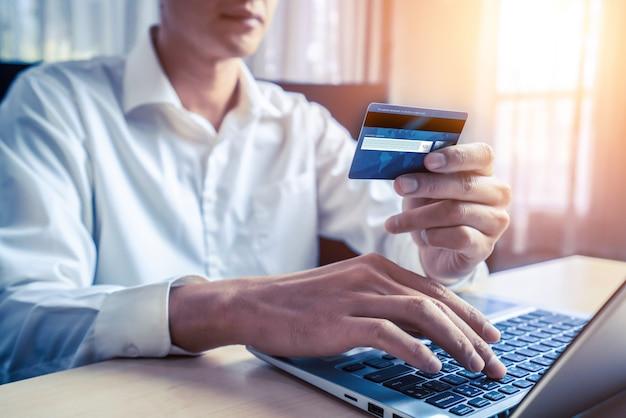 Jeune homme utilise une carte de crédit pour faire des achats en ligne sur une application informatique ou un site web. concept de commerce électronique et de magasinage en ligne.