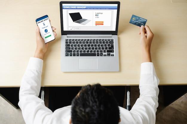 Jeune homme utilise une carte de crédit pour faire des achats en ligne sur une application informatique ou un site web.