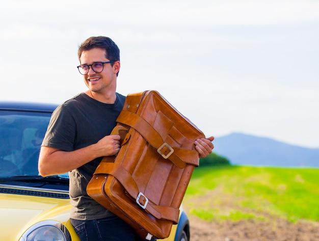 Jeune homme avec valise de voyage