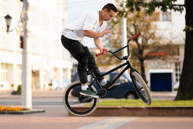 Un jeune homme sur un vélo bmx enveloppe le volant dans un saut. pour n'importe quel but.