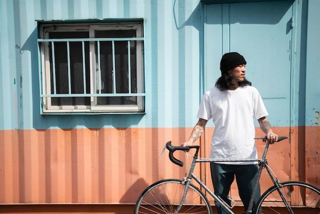 Jeune homme avec un vélo dans la ville