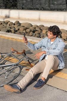 Jeune homme avec un vélo à l'extérieur